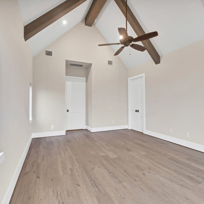 Master bedroom with cedar beams accenting the cathedral ceiling
