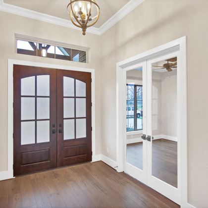 Craftsman style double front doors welcome you into tall ceilings at foyer
