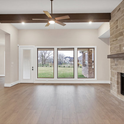 Floor to ceiling natural stone fireplace gently warms the room & transforms the space